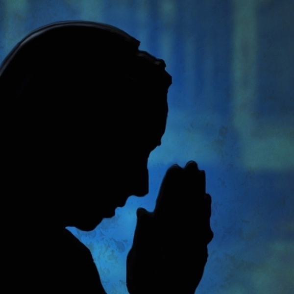 silhouette of a nun praying
