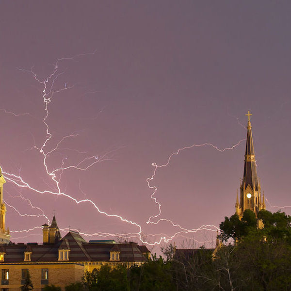 the Golden Dome and the Basilica of the Sacred Heart lit up under criss-crossing lightning